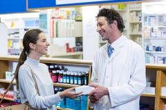Farmacista che assiste le pillole al cliente fotografia stock