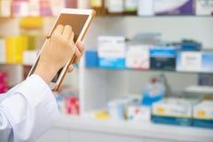 Farmacista che lavora con un computer della compressa nella farmacia che lo tiene in sua mano mentre leggendo informazioni immagini stock libere da diritti
