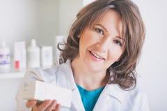 Farmacista che mostra una medicina nella farmacia fotografia stock