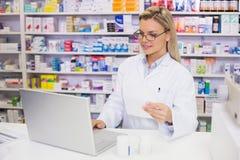 Farmacista che per mezzo del computer Fotografia Stock