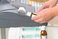 Farmacista che per mezzo del registratore di cassa Immagini Stock Libere da Diritti