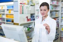 Farmacista che prende nota di prescrizione tramite il computer fotografia stock