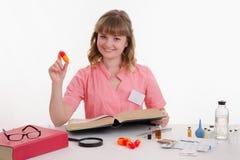 Farmacista che si siede alla tavola con la pillola ed il riferimento Immagine Stock