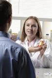 Farmacista che spiega prescrizione al paziente Fotografie Stock Libere da Diritti