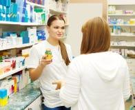 Farmacista che suggerisce droga medica al compratore Fotografie Stock Libere da Diritti
