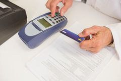 Farmacista che usando tastiera e tenendo la carta di credito Immagine Stock Libera da Diritti