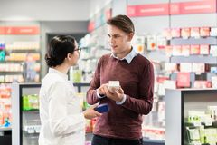 Farmacista con esperienza che controlla le indicazioni di un Ne della medicina fotografie stock