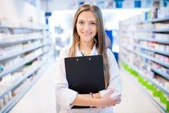 Farmacista con la lavagna per appunti ed i farmaci da vendere su ricetta medica Fotografie Stock Libere da Diritti