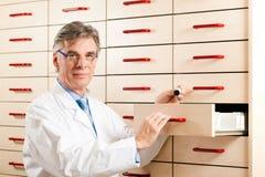 Farmacista davanti alla cassa di medicina Fotografie Stock