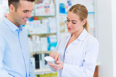 Farmacista e cliente alla farmacia fotografia stock libera da diritti