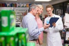 Farmacista ed i suoi clienti che parlano del farmaco Fotografia Stock Libera da Diritti