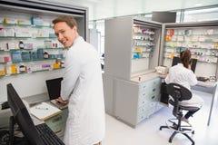 Farmacista felice che per mezzo del computer Fotografia Stock Libera da Diritti