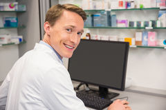 Farmacista felice che per mezzo del computer fotografie stock