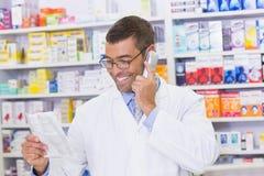 Farmacista felice sul telefono immagine stock