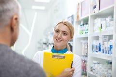 Farmacista femminile adorabile che aiuta il suo cliente fotografia stock libera da diritti