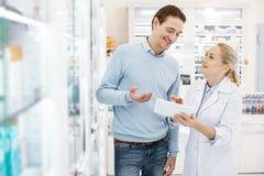 Farmacista femminile affascinante che trova farmaco fotografia stock