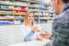 Farmacista femminile che serve un cliente maschio fotografia stock libera da diritti
