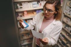 Farmacista femminile con la prescrizione che controlla medicina fotografia stock libera da diritti