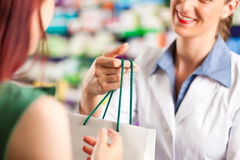 Farmacista femminile nella sua farmacia con un cliente Immagini Stock Libere da Diritti