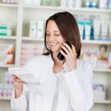 Farmacista Holding Prescription Paper mentre per mezzo del telefono senza cordone Immagini Stock