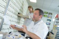 Farmacista maschio disabile che sceglie memorizzando le medicine Fotografia Stock