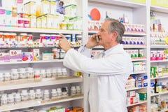 Farmacista messo a fuoco sul telefono che indica medicina Immagini Stock