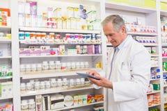 Farmacista senior che per mezzo del pc della compressa Immagine Stock
