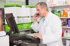 Farmacista senior che telefona mentre per mezzo del computer Fotografia Stock Libera da Diritti