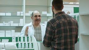 Farmacista senior positivo che dà la medicina del cliente alla farmacia immagine stock