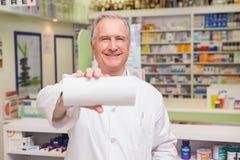 Farmacista senior sorridente che mostra carta Fotografia Stock