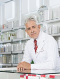 Farmacista sicuro Leaning On Counter in farmacia fotografia stock