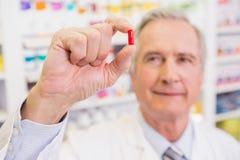 Farmacista sorridente in cappotto del laboratorio che mostra pillola Fotografia Stock