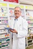 Farmacista sorridente che per mezzo del pc della compressa Fotografie Stock Libere da Diritti