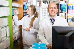 Farmacista sorridente che sta allo scrittorio di paga Fotografie Stock Libere da Diritti