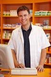 Farmacista sorridente dietro il contatore immagini stock libere da diritti