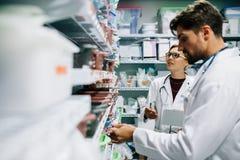 Farmacisti che controllano inventario alla farmacia dell'ospedale fotografie stock
