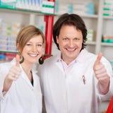 Farmacisti sicuri che mostrano il segno di Thumbsup Immagine Stock