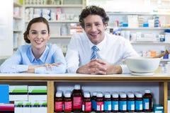 Farmacisti sorridenti che pendono al contatore in farmacia fotografie stock
