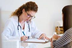 Farmaco di prescrizione di medico femminile per il paziente nell'ufficio fotografia stock libera da diritti