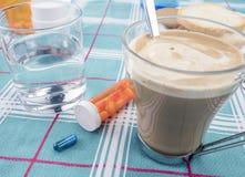 Farmaco durante la prima colazione, capsule accanto ad un bicchiere d'acqua, immagine concettuale immagine stock
