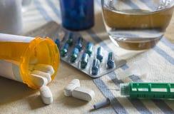Farmaco durante la prima colazione, capsule accanto ad un bicchiere d'acqua, immagine concettuale fotografia stock