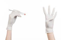 Farmacología y tema médico: la mano del doctor en un guante blanco que sostiene las pinzas con la cápsula roja de la píldora aisl Fotografía de archivo libre de regalías