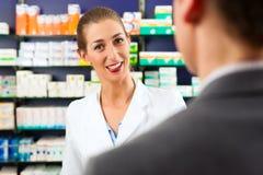 Farmacéutico de sexo femenino con el cliente en farmacia Fotografía de archivo libre de regalías