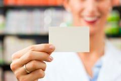 Farmacéutico de sexo femenino con la tarjeta de visita en farmacia Fotos de archivo