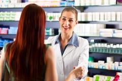 Farmacéutico de sexo femenino en su farmacia con un cliente Fotos de archivo libres de regalías