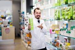 Farmacéutico de sexo masculino sonriente que muestra píldoras derechas Imagen de archivo