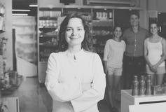 Farmacéutico feliz de la mujer que se coloca entre estantes Imagenes de archivo