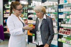 Farmacêutico que recomenda a medicamentação ao paciente superior. Foto de Stock