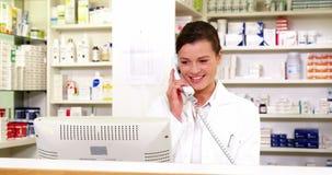 Farmacéutico que se coloca en el contador y que habla en el teléfono almacen de metraje de vídeo