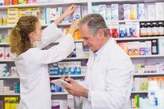 Farmacéuticos que buscan medicinas con la prescripción Foto de archivo libre de regalías